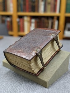 A thick leather bound book with clasps.