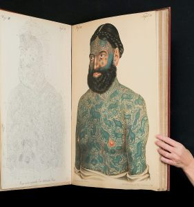 Photograph of an opening of a two foot high book showing a tattooed man.