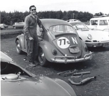 A man in sunglasses and overalls stands next to a Volkswagan bug with the racing number 77 painted on it.
