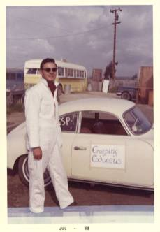 "A man in sunglasses and white coveralls stands next to a small white sports car with the sign Creeping Caduceus"" taped to it."