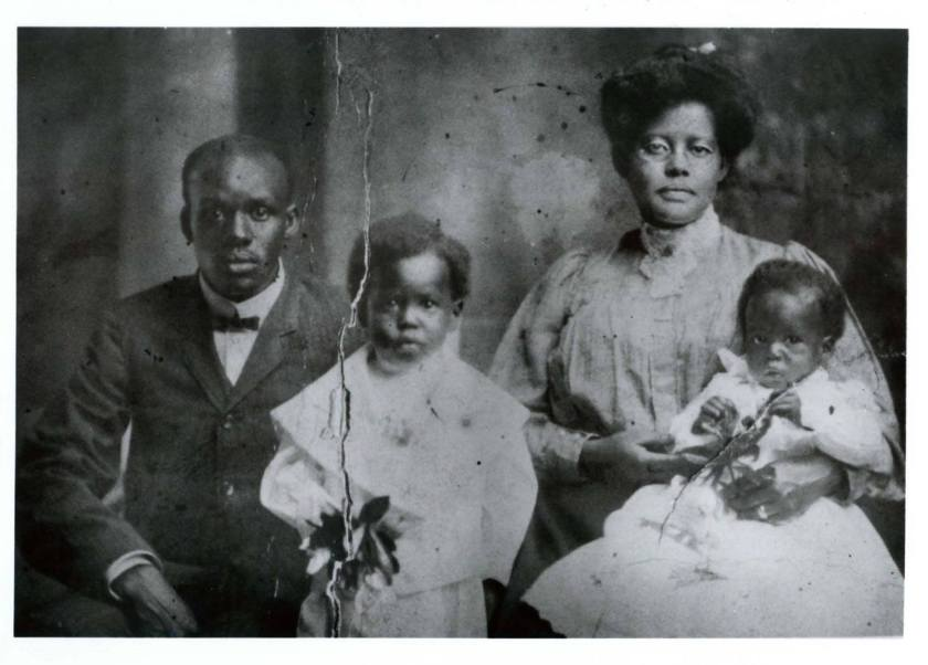 An African American family with two young children sit for a formal portriat.