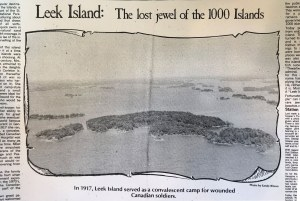 A halftone photograph from an article of an aerial view of a long wooded island surrounded by smaller islands.