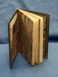 An open book showing gold embossing and decorative endpapers.