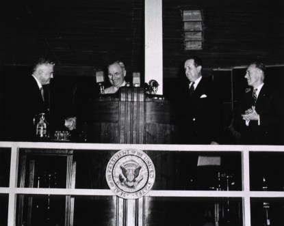President Harry Truman stands at the podium with 3 other guests at the cornerstone ceremony of the NIH Clinical Center on June 22, 1951.