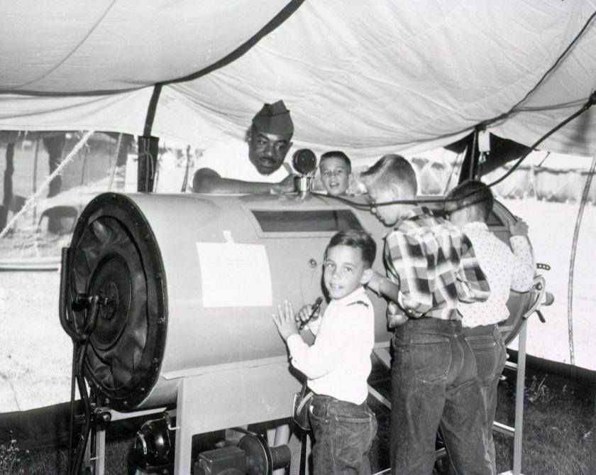 Children gather around and inspect a large cylindrical machine under the supervison of a soldier..
