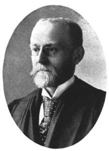 A formal photograph of a middle aged white man wearing a suit and tie and academic robe.