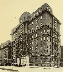 A historic photograph of a nine story stone building on a city street corner.