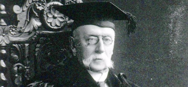 A photograph of a man in academic robes in an ornate wooden chair.