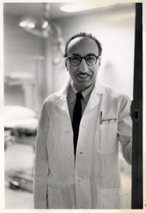 DeBakey poses in a doorway in a labcoat.