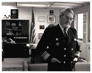A white man in a military uniform stands in an office in front of an American flag.