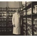 A photograph of a man in a lab coat standing in a storeroom full of glass bottles.