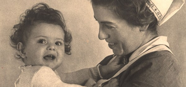 A nurse in a cap smiling at a young child.