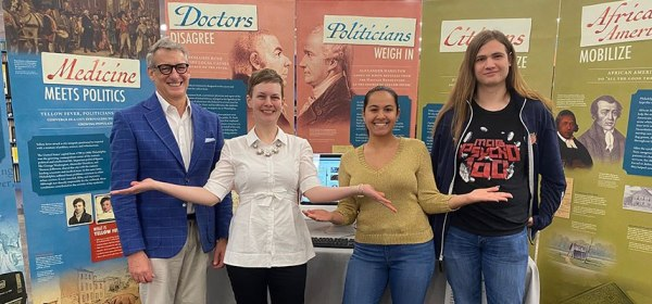 Isabella Michal and colleagues pose in front of the installed Politics of Yellow Fever banners.