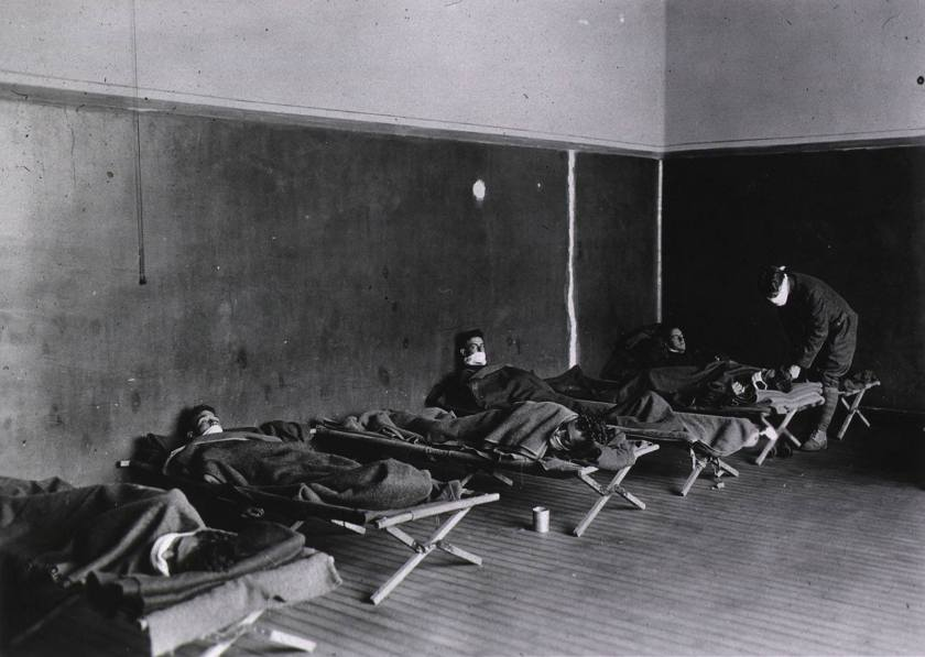 Men wearing white cloth masks lay on wooden cots under wool blankets in a bare room.