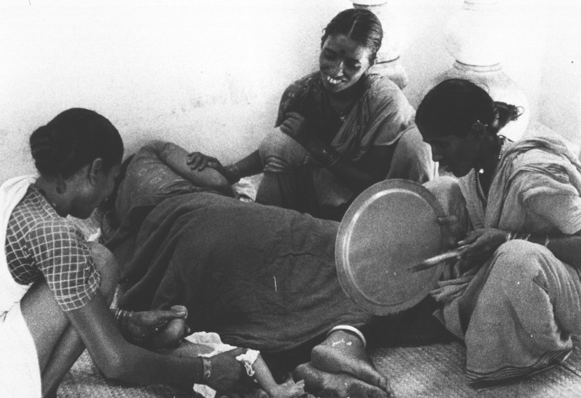 A midwife helps a woman through childbirth; two other woman offer assistance, one of which is beating a tin tray, the traditional way to make the baby cry.