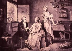 Showing a country doctor, in a farm-house setting, with two women and a baby, a cow links in at the door.
