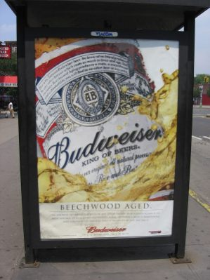 An advertisment for beer featuring a can on a shelter on a city street.