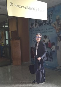 A woman in the lobby of the National Library of Medicine under the History of Medicine Division sign.