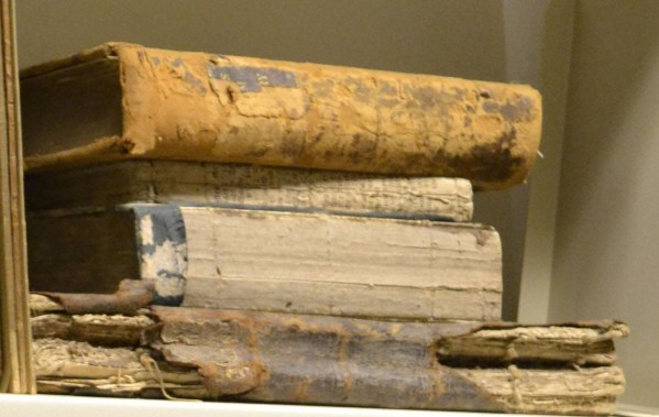Books with missing spines and covers and leather binding deteriorating into scraps and powder.