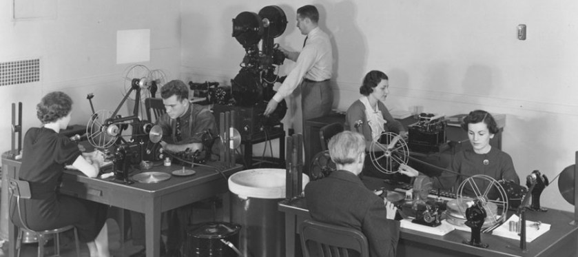 NARA Photograph of white women and men working as archival catalogers winding through and watching motion picture films