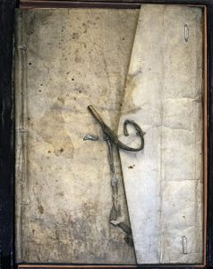 A book in an undecorated envelope, sewn and closed with a leather thong.