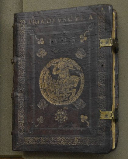 A book with dark leather cover embossed and filded with words, flowers and a man on a horse with a sword, and metal clasps.
