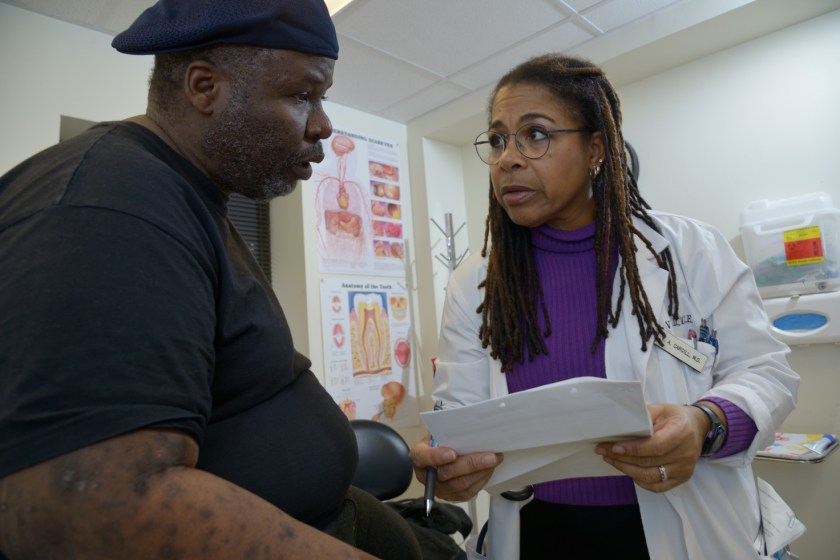 A black woman in a lab coat shares a document with a black man in a medical office.