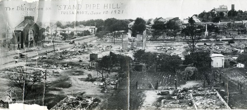 A photograph from a hilltop shows the utter destruction of several city blocks.