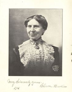 Photograph of an older white woman in a dark jacket with lace front.
