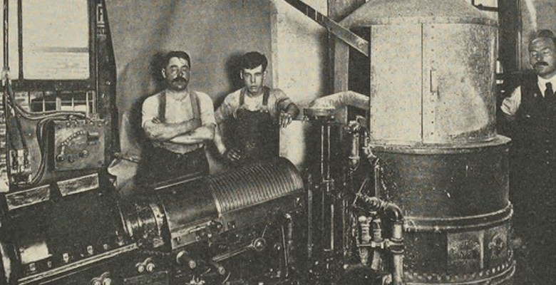 Three white men stand in a printing factory