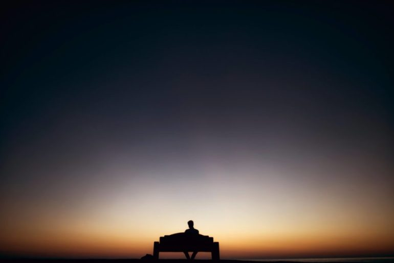 Man sits alone watching the sunset. Socialisation of men influences how they treat women and keeps misogyny at bay.