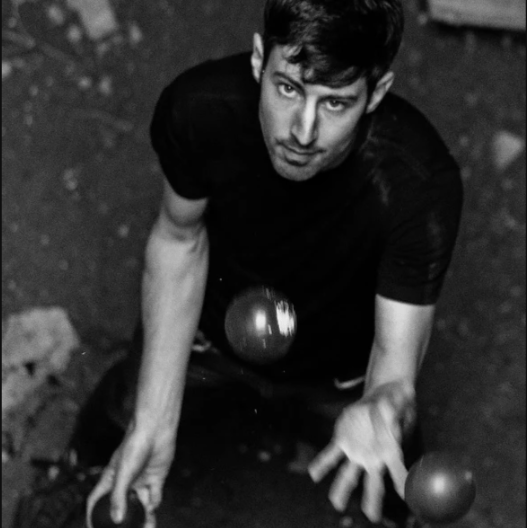 Christian juggling a lot of juggling balls and looking fire