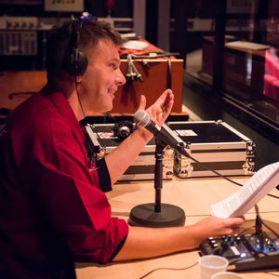 Dave van der Wal achter de microfoon met koptelefoon op.