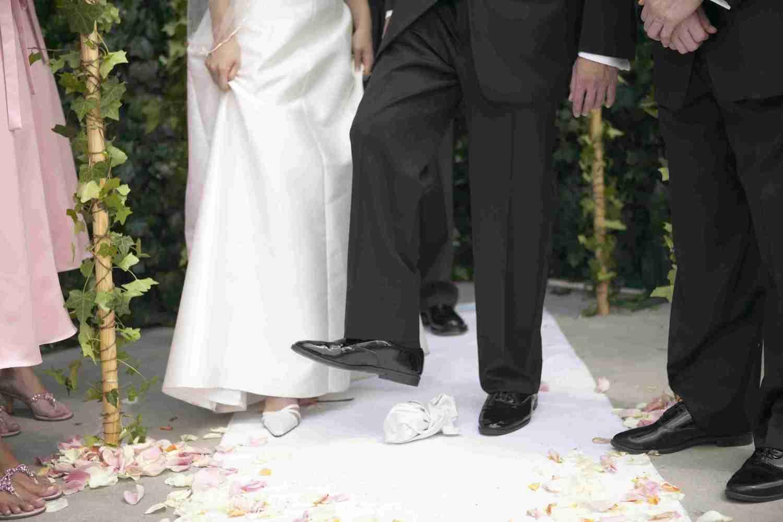 Nach jüdischer Tradition zertritt der Bräutigam mit dem Schuh ein Glas. Man sieht den Fuß des Bräutigams sowie die Füße der umstehenden Gäste und der Braut. | Bildquelle: Mauritius
