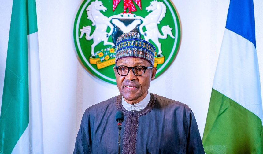 President Buhari on African Attire, hat and glasses standing