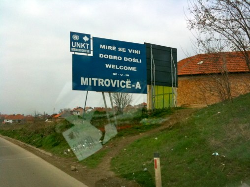 Welcome sign for Mitrovica, erected by United Nations Kosovo Team (UNKT). This is one of few signs that has not become defaced. Mitrovica, Kosovo.