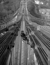 Novembre 1930: Les ouvriers repeignent le pont suspendu du détroit de Menai qui relie l'île d'Anglesey au Gwynedd (Pays de Galles).