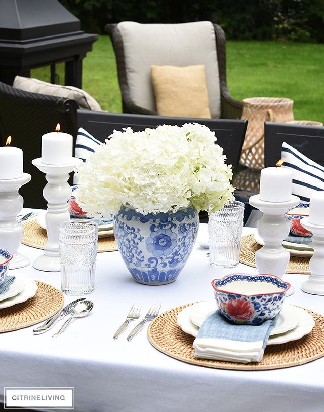 Outdoor late summer tablescape with blue and white vase and hydrangeas.