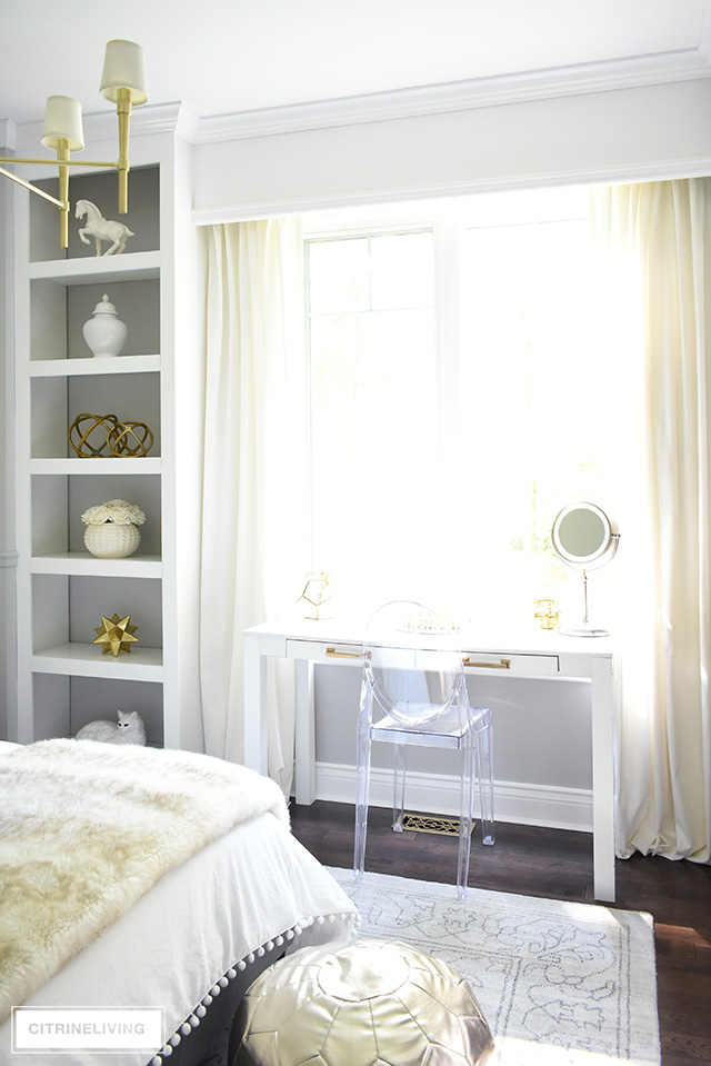 Glamorous and chic bedroom vanity with a Louis Ghost chair to complete the look!