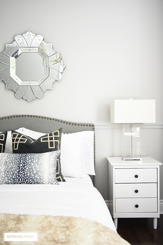 Gorgeous teen girl doing make-up in a beautiful and tailored gray upholstered bed with brass nailhead trim, venetian style mirror and glam crystal table lamps. Layers of pattern and textures on the upholstered bed are fashion-forward and chic!