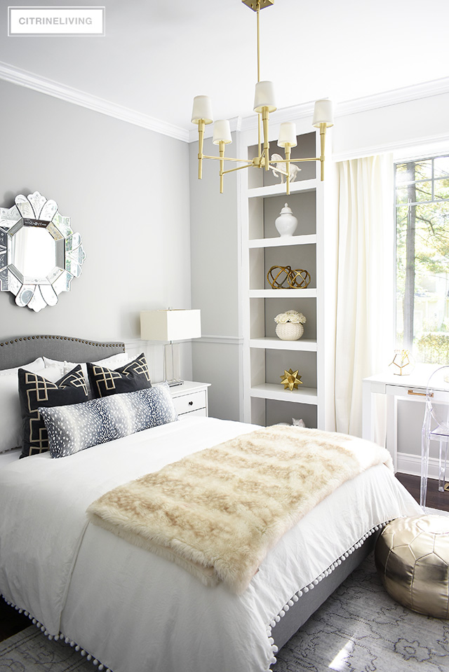 A fabulous fashion-forward teen girl dressing up with chic and elegant details - gray upholstered bed with brass nailhead trim, soft layers of pompom bedding.