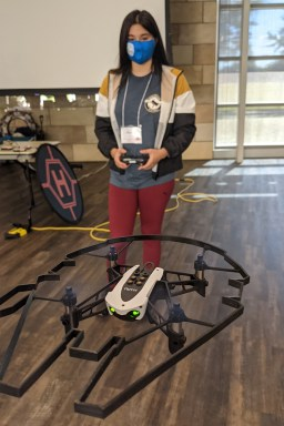 A student with long dark hair wearing a face mask pilots a mini-drone using a handset.