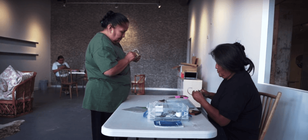 Two Native American women working on jewlery