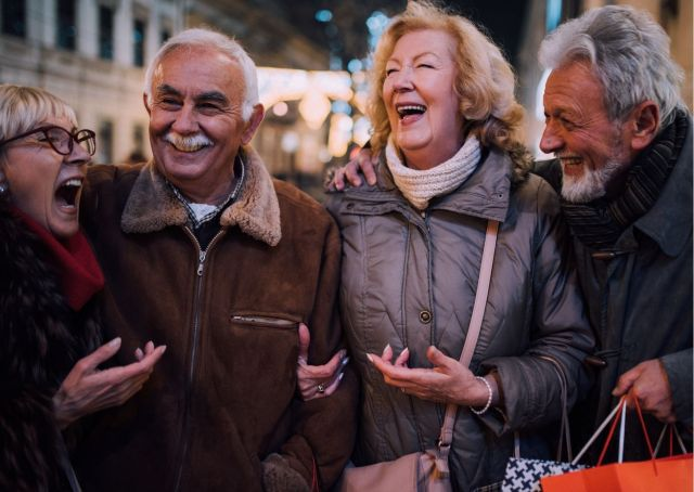 Group of older people laughing and talking together outdoors