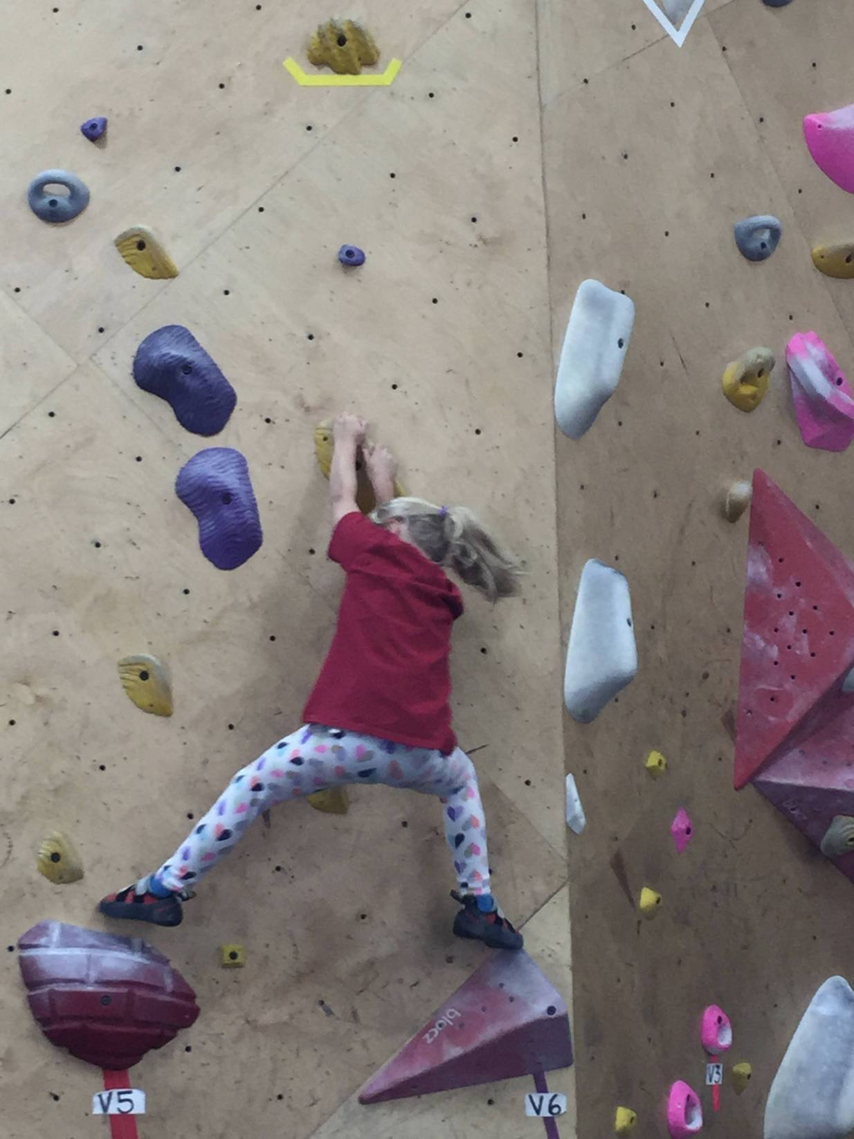 Wylie reaching for the next hold on the wall at Brooklyn Boulders in Somerville.