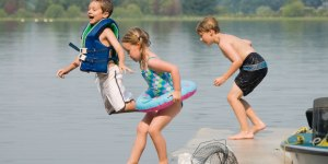 Barn som hopper i vannet