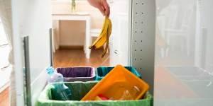 Hånd kaster søppel i søppelskap