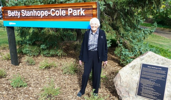 Betty Stanhope-Cole in front of the park sign, named in her honour and beside a boulder with a plaque listing her accomplishments. Photo courtesy of Ted Smith, 2011.