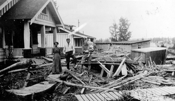 Family in front of a house where the dirt street is littered with wood debris brought in by the flood. Image courtesy of the City of Edmonton Archives EA-25-1.