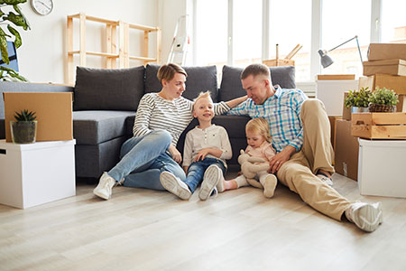 A family sitting in front of a couch enjoying their new home